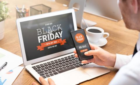 Man looks at Black Friday e-commerce offer on laptop and mobile © Proxima Studio - shutterstock