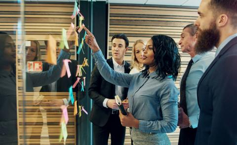 Creative group of business people brainstorming putting sticky notes on glass wall in office © Flamingo Images - Shutterstock